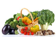 Mixed vegetables. Seasonal vegetables on white background with wicker basket Royalty Free Stock Photo