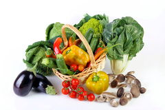 Mixed vegetables. Seasonal vegetables on white background with wicker basket Royalty Free Stock Photography