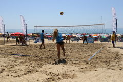 Mixed volleyball. Girl making kickoff at a beach volleyball game alongside a guy playing with her Royalty Free Stock Photography