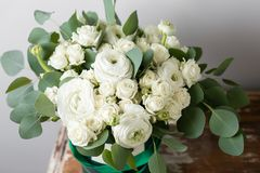 Mixed white flowers . Bouquet of spray roses and ranunculuses in a box on wooden table. copy space. Mixed white flowers . Bouquet of spray roses and Stock Images