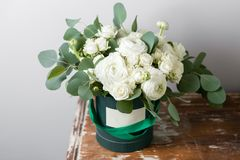 Mixed white flowers . Bouquet of spray roses and ranunculuses in a box on wooden table. copy space. blank for text.  Royalty Free Stock Image