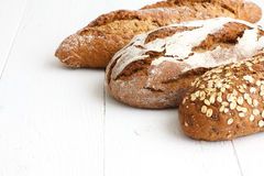 Mixed whole grain health breads on rustic white painted wood Royalty Free Stock Photography