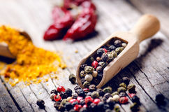Mixed whole pepper on a wooden scoop. Natural old background. Concept of food, spice Royalty Free Stock Photography
