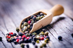 Mixed whole pepper on a wooden scoop. Natural old background. Concept of food, spice Royalty Free Stock Photos