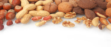 Mixed whole and shelled nuts in a banner. Mixed whole and shelled nuts in a horizontal banner including hazelnuts, brazil nuts, peanuts or groundnuts and walnuts Stock Images
