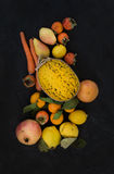 Mixed yellow orange fruit and veggies assortment, ingredients for smoothie. Melon, garnet, grapefruit, carrot, persimmon Stock Image