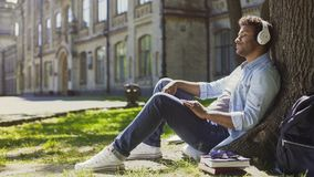Mixed young male sitting under tree in headphones, eyes closed, enjoying music. Stock footage Stock Image