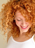 Mixed young woman with curly hair. A smiling mixed young woman with curly red hair royalty free stock photo