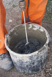 Mixer attachment on a drill. Builder stirs the adhesive in the bucket stock photo