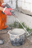 Mixer attachment on a drill. Builder stirs the adhesive in the bucket stock image