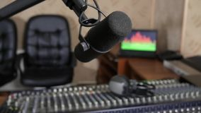 Mixer broadcast sound control and condenser microphone close-up in room of recording studios. Unfocused stock footage