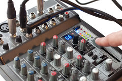 Mixer console. Sound director's finger moving the volume fader of a mixing console Stock Photos