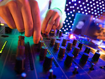 Mixer in nightclub. Hand of DJ on the mixer in nightclub Royalty Free Stock Photography