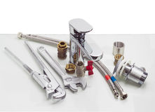 Mixer tap, plumber wrench, adjustable wrench and several plumbin Royalty Free Stock Image