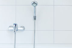 Mixer tap and shower head. In front of white flagging Stock Images