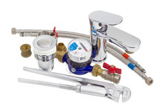 Mixer tap, water meter, plumber wrench and some plumbing compone Royalty Free Stock Images