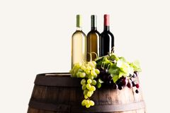 Mixes of bottle ow wine on barrel. With grape on white background stock image