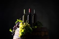 Mixes of bottle ow wine on barrel. With grape om dark background royalty free stock photos