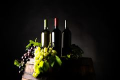 Mixes of bottle ow wine on barrel. With grape om dark background royalty free stock photography