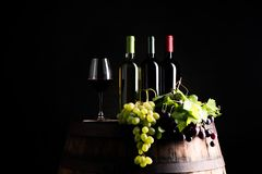 Mixes of bottle ow wine on barrel. With grape om dark background stock photos