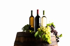 Mixes of bottle ow wine on barrel. With grape on white background stock photography