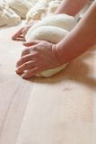 Mixing. Woman hands at work mixing two dough on the counter royalty free stock photo