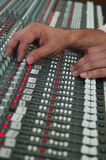 Mixing audio tracks. Sound technician's hand on audio mixer Stock Images