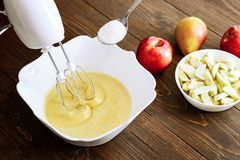 Mixing Batter or dough for apple-pear cake or muffin or pancake. Close up in wooden table c ingredients.  stock images