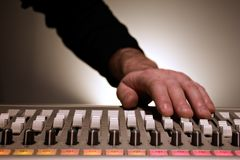 Mixing Board. Hand adjusting sliders on a mixing board Royalty Free Stock Image