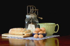 Mixing bowl, Eggs and Bread. Still life of vintage mixing bowl, fresh brown eggs, antique butter churn and bread royalty free stock photo