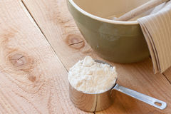 Mixing bowl and measuring cup. A measuring cup full of flour sits next to a green mixing bowl with a wooden spoon and brown striped towel all on top a wooden Stock Photography
