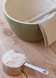 Mixing bowl and measuring cup. A measuring cup full of flour sits next to a green mixing bowl with a wooden spoon and brown striped towel all on top a wooden Stock Photos