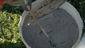 Mixing cement in a bucket stock video