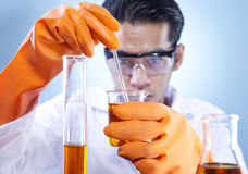 Mixing chemical in laboratory. A scientist mixing chemical in laboratory Royalty Free Stock Images