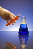 Mixing Chemicals. A latex gloved hand ready to pour a liquid from a test tube into a beaker on a blue background stock photos