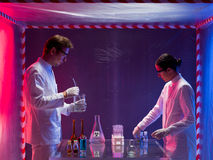 Mixing chemicals in a containment tent. Two scientists, a men and a woman, working with chemicals in a containment tent, lit by a gradient red and blue light royalty free stock image