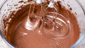 Mixing chocolate cream, batter or dough with mixer stock video