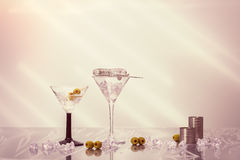 Mixing Cocktails. Mixing Martini cocktails over ice in Art Deco glasses with olives royalty free stock photos