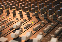 Mixing console. Sound mixing console lit by an incandescent lamp.  Very shallow DOF Stock Photo