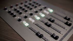 Mixing console also called audio mixer, sound board, mixing deck or mixer is an electronic device stock video footage