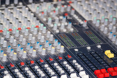 Mixing Console. In professional audio, a mixing console, or audio mixer, also called a sound board, mixing desk, audio production console, or mixer is an Stock Photo
