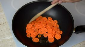Mixing cut carrots. Adding and mixing cut carrots in a wok with a mixing spoon during a cooking process stock video