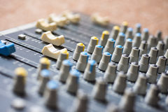 Mixing desk controls. An angled image of a mixing desk, showing control knobs and sliders Stock Photo
