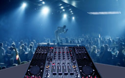 Mixing desk in nightclub party with lightshow. Mixing desk with sound mixer is pictured in a rave party in nightclub party royalty free stock images