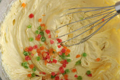 Mixing dough for cake in a bowl with candied fruit. And whisk Stock Photography