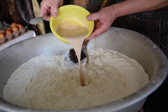 Mixing dough by female hands at home with old spoon Royalty Free Stock Photos