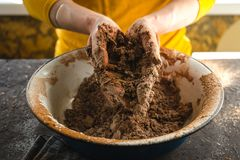 Mixing the dough with your hands in a large bowl side view Stock Photo