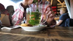 mixing Dutch mint in glass cup tea stock footage
