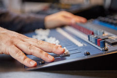 Mixing engineer moving the sliders of audio console Stock Image