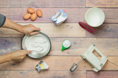 Mixing flour, eggs, butter and sugar to cook a cake stock image